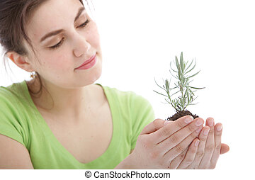 Beautiful woman holding a young plant