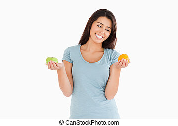Beautiful woman holding an apple and an orange