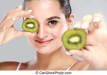 beautiful woman holding and showing slices of kiwi