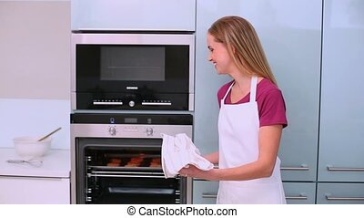 Beautiful woman holding baking tray with biscuits in kitchen