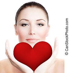 Beautiful woman holding big red heart
