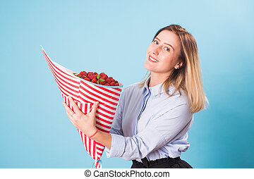 Beautiful woman holding bouquet made of strawberry