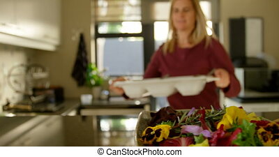 Beautiful woman holding food tray in kitchen at home 4k