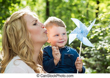 Beautiful woman holding her son a blowing the paper windmill