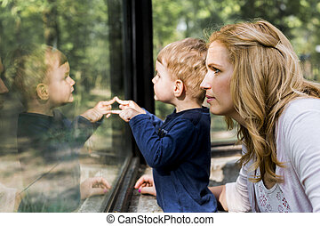 Beautiful woman holding her son with his reflection showing on the window