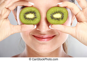 beautiful woman holding kiwi fruits in front of her eyes