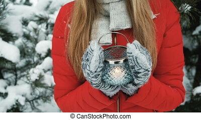 Beautiful woman holding lantern on background of winter landscape.