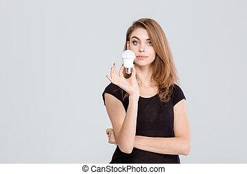 Beautiful woman holding light bulb