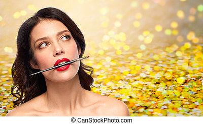 beautiful woman holding make up brush for lipstick