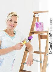 Beautiful woman holding paint brush