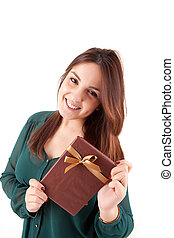 Beautiful woman holding presents while smiling over white background
