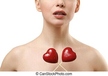 Beautiful woman holding rwo red hearts crossed.