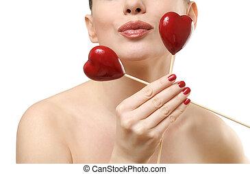 Beautiful woman holding rwo red hearts.
