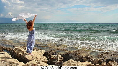 """Beautiful woman holding scarf, standing on rocks, strong woman enjoying freedom"""