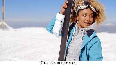 Beautiful woman holding skis with copy space - Single...