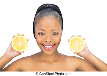Beautiful woman holding slices of orange and looking at camera