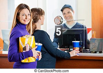 Beautiful Woman Holding Snacks While Friend Buying Movie Tickets