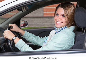 Beautiful woman holding steering wheel in car