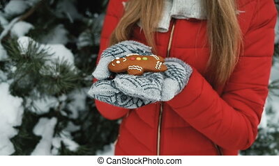 Beautiful woman holds in hand gingerbread little man, winter landscape