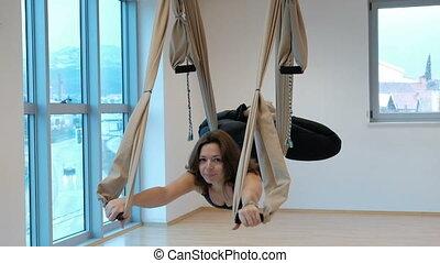 Beautiful woman hovers in hammock in aerial space of studio indoors.