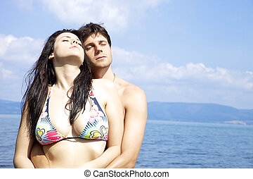Beautiful woman hugged by handsome man in the water