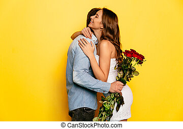 Beautiful woman hugging her boyfriend after getting bouquet of roses