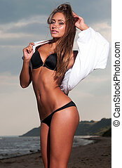 beautiful woman in a bathing suit standing on the beach