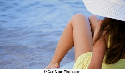 beautiful woman in a big white hat sunbathing on a deckchair