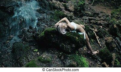 beautiful woman in a bikini standing near a waterfall