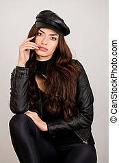 Beautiful woman in a black leather jacket and cap