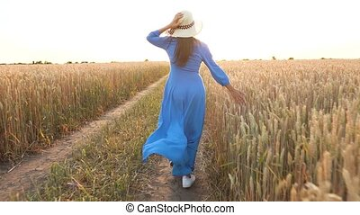 Beautiful woman in a blue dress and hat runs through a wheat field at sunset. Freedom concept. Wheat field in sunset