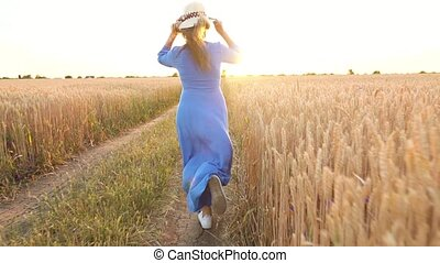 Beautiful woman in a blue dress and hat runs through a wheat...