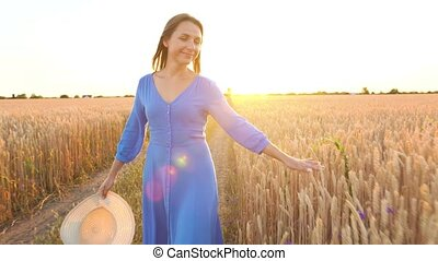 Beautiful woman in a blue dress and hat walking through a wheat field at sunset. Freedom concept. Wheat field in sunset