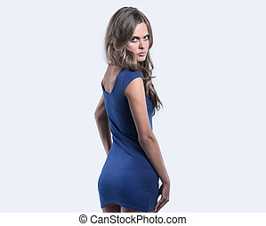 Beautiful woman in a blue dress posing on a white background