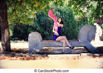 Beautiful woman in a blue dress sitting on a bench in the park