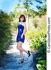 Beautiful woman in a blue dress walks in the park