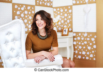 Beautiful woman in a brown dress posing on the sofa