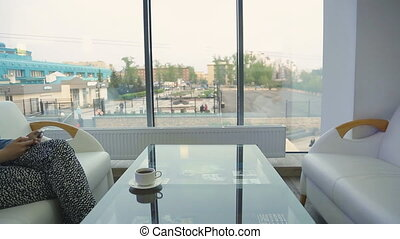 Beautiful woman in a cafe, using smartphone sitting alone in a cafe with large panoramic windows, comfortable on the couch and typing a message