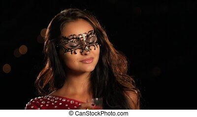 Beautiful woman in a carnival mask on black