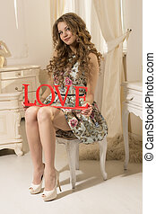 Beautiful woman in a dress sitting on a chair