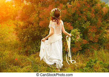 beautiful woman in a field with flowers at sunset