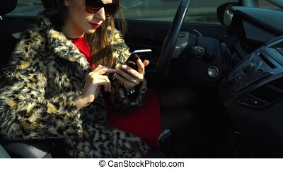 Beautiful woman in a fur coat using a smartphone and drinking coffee in the car