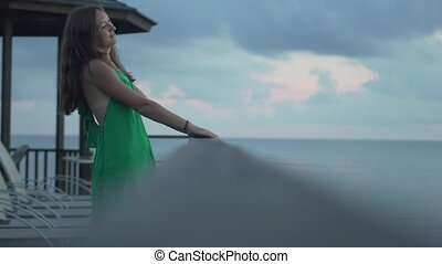 Beautiful woman in a green dress is standing on the pier