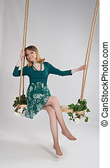 beautiful woman in a green dress on a swing