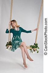 beautiful woman in a green dress on a swing