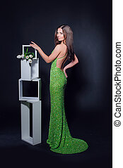 beautiful woman in a green evening dress on a black background