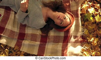 Beautiful woman in a hat and sunglasses is lying on a plaid...