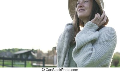 Beautiful woman in a hat at sunset in the summer on a farm.