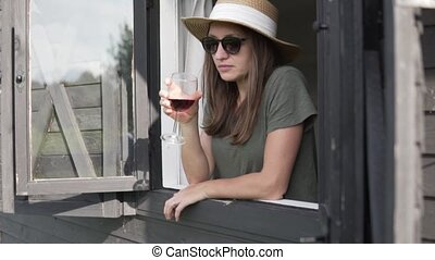 Beautiful woman in a hat is drinking red wine on a farm.