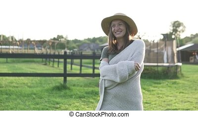 Beautiful woman in a hat walks at sunset on an eco-farm